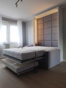 łóżko w szafie z sofą i ławostół