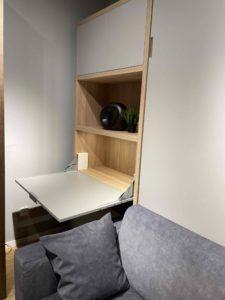 łóżko w szafie z sofą i biurkiem